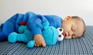 Сон – это физиологическое состояние покоя, необходимое малышу в 1 год для полноценного роста, нормального психологического и физического развития. Сон выполняет защитные функции и дает возможность всем органам восстановиться для регулирования обменных процессов и противостояния агрессивным внешним воздействиям. Отвечая на вопрос, сколько времени в сутки должен спать грудничок, следует учитывать его возраст и характер. Сколько должен спать малыш в 1 год У некоторых детей практически с рождения устанавливается стабильный режим дня, претерпевающий плавные изменения по мере взросления. Они засыпают без укачиваний и уговоров, подолгу спят, самостоятельно засыпают, проснувшись ночью. Их родители не испытывают проблем, связанных со сном малютки. К сожалению, число таких младенцев невелико. В большинстве случаев ребенок нуждается в помощи близких, чтобы уснуть. Знания о том, сколько в среднем кроха спит в сутки, помогут избежать следующих проблем: • недостатка сна для развития мозга и функционирования различных систем организма; • накопления усталости (гиперусталость); • плохого настроения; • переутомления; • снижения внимания и скорости усвоения новых навыков; • риска возникновения в будущем гиперактивности и трудностей с поведением. Сон должен гарантировать качественный отдых малютки, его усредненная длительность является примерным ориентиром для родителей. Недосыпание может привести к расстройству нервной системы и хроническому переутомлению. Излишний сон также не приносит пользы, ребенок становится вялым, раздражительным, часто просыпается по ночам. В общей сложности годовалый малыш должен спать 12-14 часов в сутки, из них 2-3 часа днем. При позитивном поведении ребенка отклонения на 1-2 часа от нормы считаются допустимыми. Как определить, что ребенку пора спать Малыш в год не всегда явно демонстрирует признаки усталости. Он может энергично двигаться, играть, бодро улыбаться, когда в действительности уже сильно устал и хочет спать. Если у малютки есть проблемы с засыпан