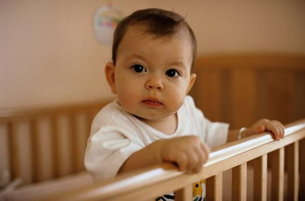 Малыш выглядывает из кроватки