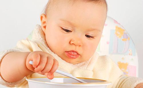 Малыш учится есть ложкой