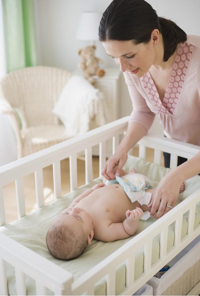 Мама меняет подгузник малышу