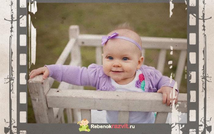Девочка 10 месяцев стоит в кроватке